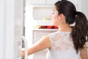 mother searching food in fridge