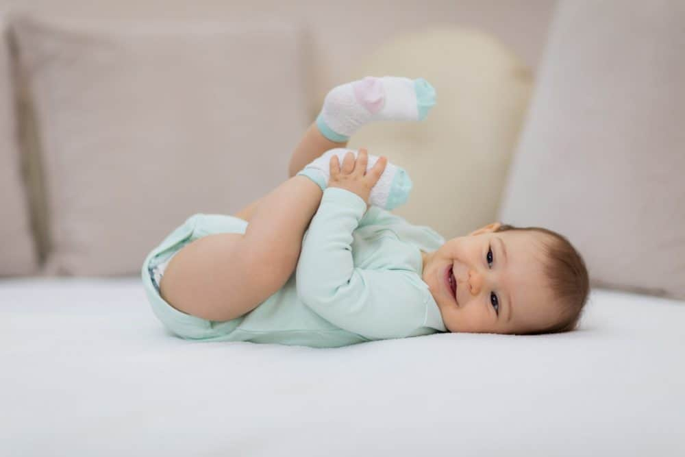 Playful baby lying down in bed